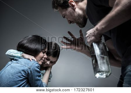 Fed up. Angry man with bottle in hand shouting at his wife and daughter lifting his arm on them, standing in semi position