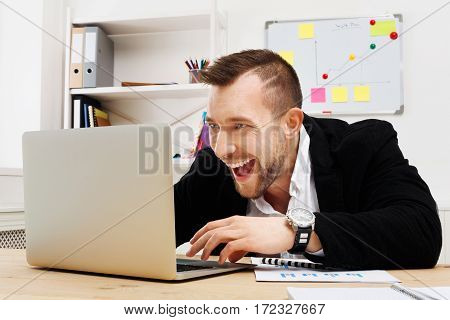 Gambling or gaming in the office. Excited young Businessman addicted to computer. Happy man looks at laptop screen, internet leisure at work