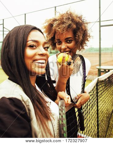 young pretty girlfriends hanging on tennis court, fashion stylish dressed swag, best friends happy smiling together. lifestyle people concept close up