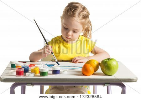 Cute little toddler child painting with paintbrush and colorful paints. Adorable baby girl drawing, sitting behind table, isolated on white background. Fresh fruits is on the table.