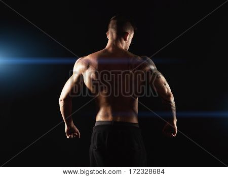 Unrecognizable man bodybuilder shows strong hands and back muscles, athletic trapezius. Low key, studio shot on black background with flare effect