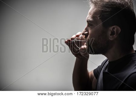 Favorite drink. Angry male person wearing grey T-shirt keeping small glass near his lips standing in semi position