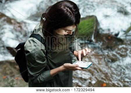 Young beautiful brunette girl with backpack looking at phone, waterfall background. Copy space.