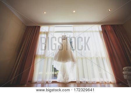 Bridal gown in hotel room beautiful wedding dress hanging in the bride's room