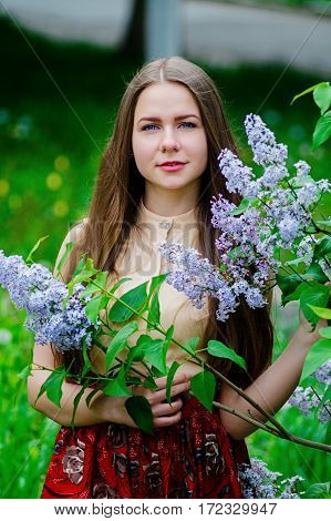 Pretty Girl With Posing At Garden Against Blooming Lilac.