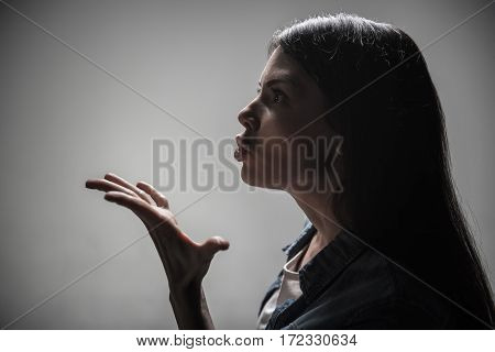 Want right decision. Serious female keeping her eyes widely opened posing in profile while standing over grey background