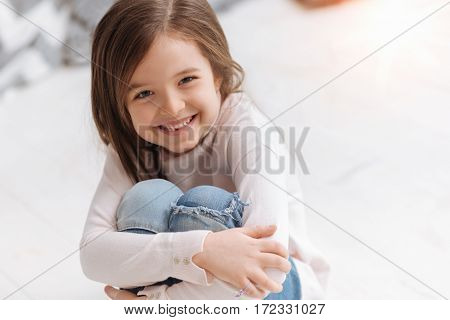 Beautiful girl. Delighted happy nice child sitting and smiling while being in the wonderful mood