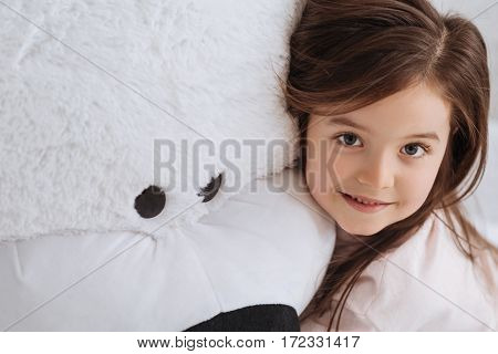 Stuffed toys. Cute pretty young girl smiling and looking at you while leaning on her stuffed toy