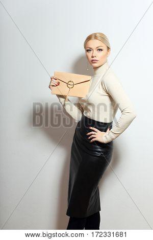 fashion model holding little purse shot in light background in studio