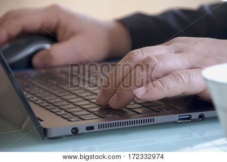 Businessman close-up view of the hands on the laptop keyboard