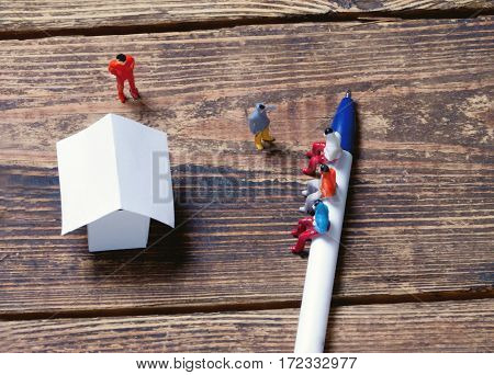 tools, toy people and paper model house on a wooden surface.view from above.toned