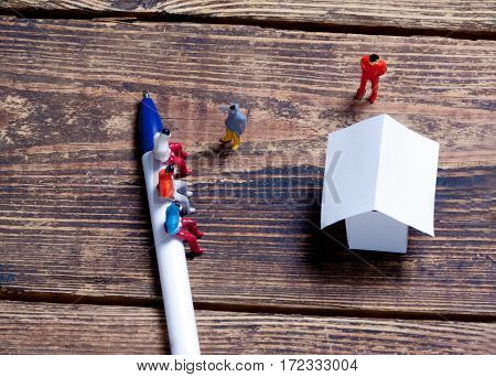 wrench, toy people and paper model house on a wooden surface.view from above