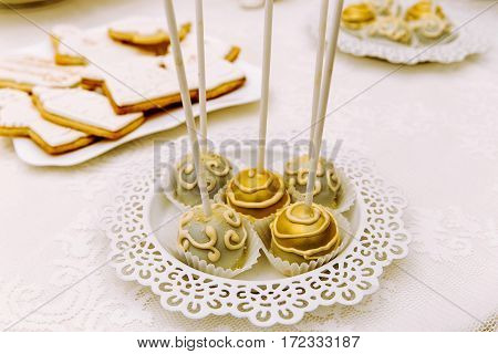 Cake pops decorated with golden and gray chocolate on white carved plate