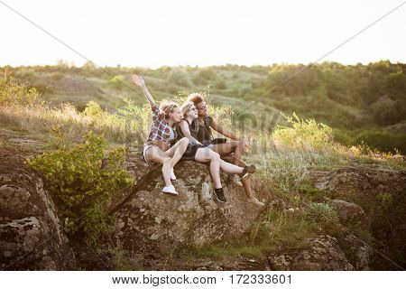 Young attractive girls smiling, sitting on rock, enjoying view in canyon. Copy space.
