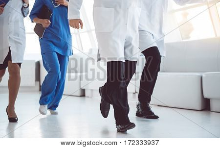 Cropped image of doctors running for help through the hospital hall