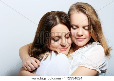Mother and teen daughter portrait hugs and love