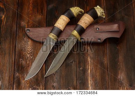Hunting damascus steel knives handmade and leather sheath on a brown wooden background closeup