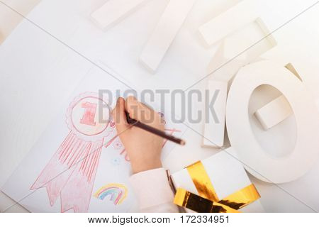 Drawing a postcard. Close up of a pencil being in hands of a nice cute creative girl while being used for drawing a postcard