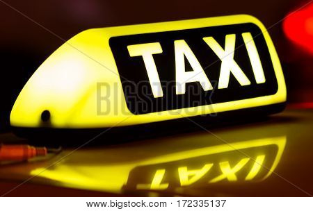Taxi sign on the roof of a car at night