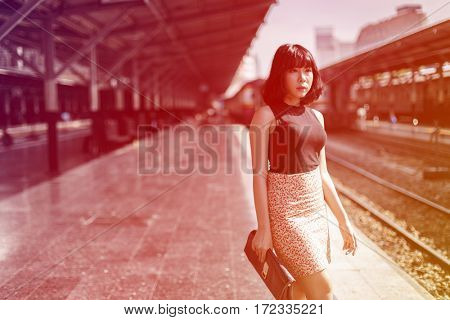 Asian ethnicity girl is at train station.