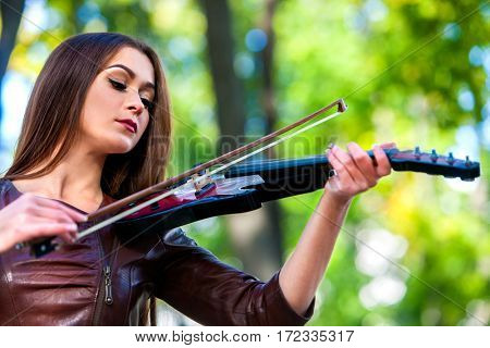 Woman perform music on violin in park outdoor. Girl performing jazz on city street . Spring outside with green tree background.