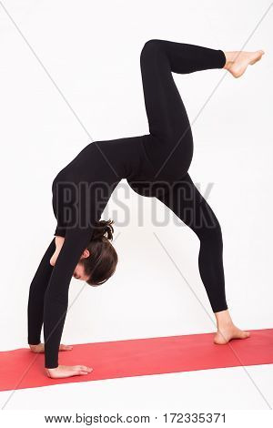 Beautiful athletic girl in a black suit doing yoga. chakrasana - bridge pose . Isolated on white background.