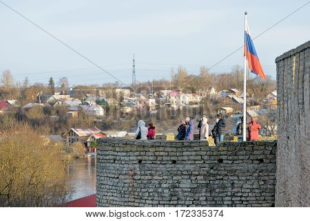 IVANGOROD, RUSSIA - JANUARY 3, 2017: Group of tourists look at the attractions on the observation deck with Russian flag of one of the towers in Ivangorod Fortress
