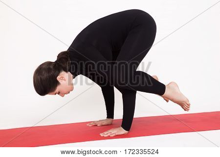 Beautiful athletic girl in a black suit doing yoga. Kakasana asana - crow pose . Isolated on white background.