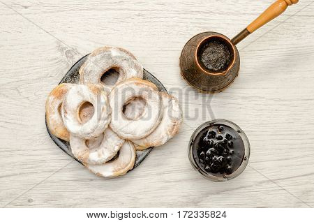 Donuts sprinkled with powdered sugar fresh coffee and jam on a light wooden fone. Top view