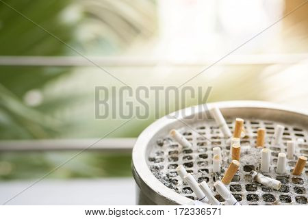 discarded cigarettes on ashtray with nature copy space background