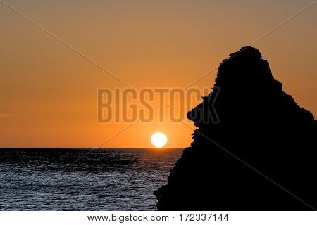 A golden sun rises past the ocean horizon while a happy face appears in silhouette from a rock stack. Seaham, County Durham, England