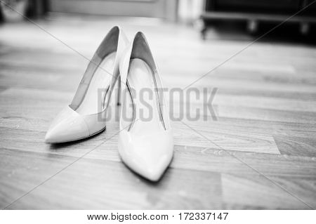Beige Wedding Shoes For Bride On Wooden Floor. Black And White Photo