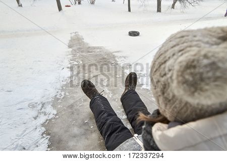 Schoolgirl sliding down on icy hill in the moscow yard