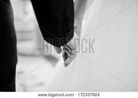 Close Up Hand In Hand Of Wedding Couple. Black And White Photo