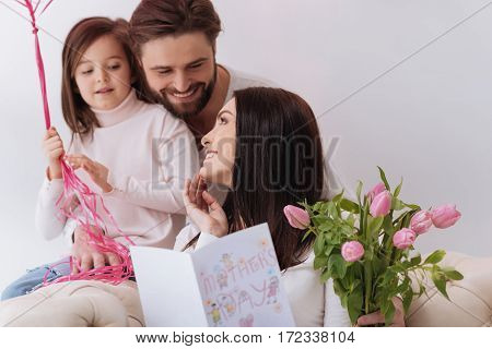 Thank you so much. Happy positive attractive woman holding a Mothers Day postcard and smiling while looking at her husband and daughter