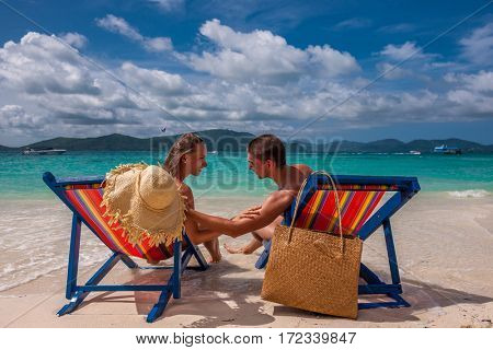 Couple on tropical beach in loungers at Thailand