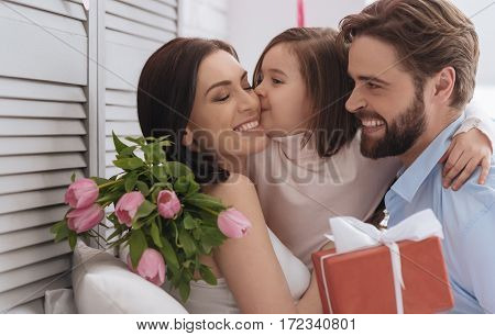 Happy family. Nice pleasant pretty girl hugging her parents and kissing her mother while celebrating Mothers Day
