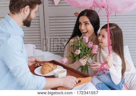 For my dear wife. Handsome nice bearded man holding a tray with breakfast and looking at his wife while celebrating Mothers Day