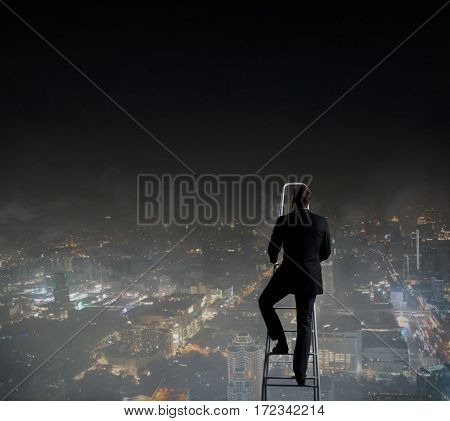 Businessman standing on stepladder over night city background.  Business, career, concept.