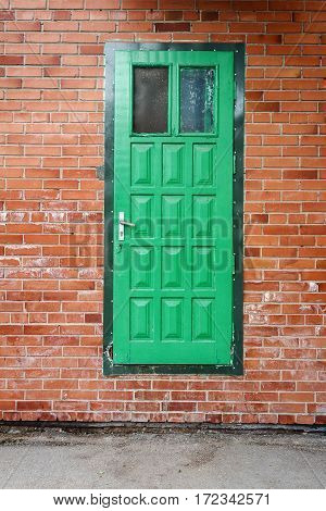 Outdoor architecture with green door on a red brick wall
