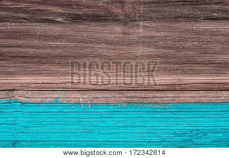 surface of an old wooden board. Half shaded sky-blue paint.