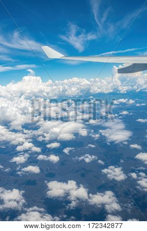 Plane flying high above the clouds. Some hills and vegetation can be seen below.