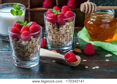 Healthy breakfast. Granola with honey yogurt and fresh berries raspberry in a glass. Selective focus