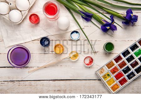 Top view of chicken eggs for coloring with paints and iris flowers on wooden table