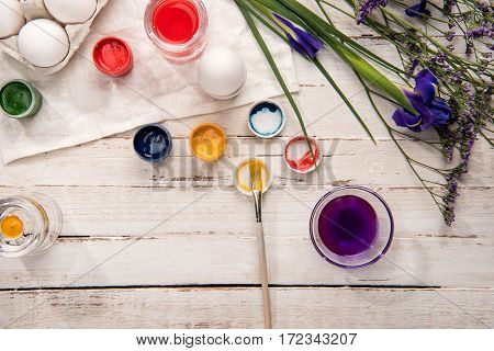 Top view of chicken eggs for coloring with paints and beautiful flowers on wooden table