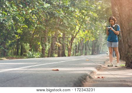 Asian woman hitchhiker with backpack looking camera on highway road with sunlight on nature background.