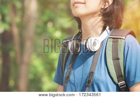 Asian glasses woman hiker with backpack breathing nature fresh air. Beautiful girl with wear headphone smiling on nature background.