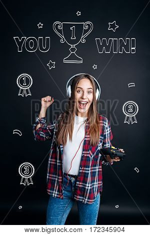 My victory. Joyful content young woman smiling and winning a round in video games while playing video games
