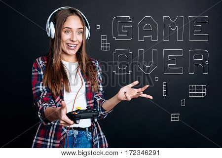 How can it be. Cheerful delighted young emotional woman smiling and playing video games while failing in a round
