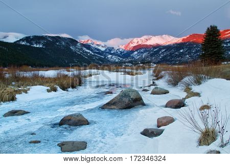 The mountain peaks light up in Moraine Park in Rocky Mountain National Park located outside of Estes Park Colorado